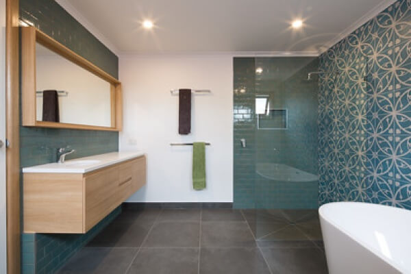 An image of a newly installed, modern bathroom, with a freestanding bath, walk in shower and patterned tiles on the walls.