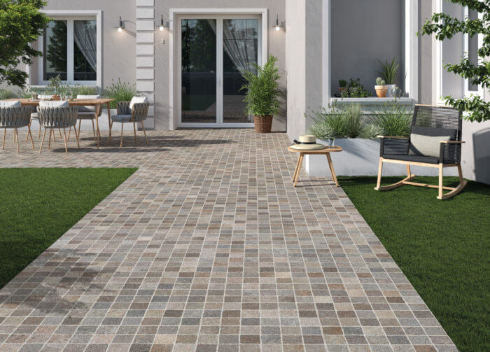 An image of a small, square tiles creating a path in a garden.